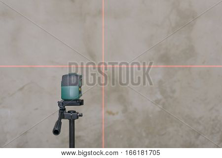 perpendicular to the rays of the laser level on the plastered wall