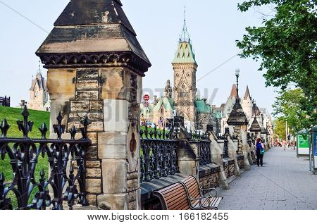 Ottawa, Canada - July 24, 2014: Canadian parliament hill building fence on sidewalk with benches