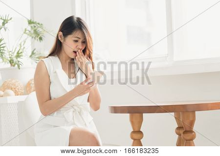 Asian woman surprised and shocked while using smart phone in white room