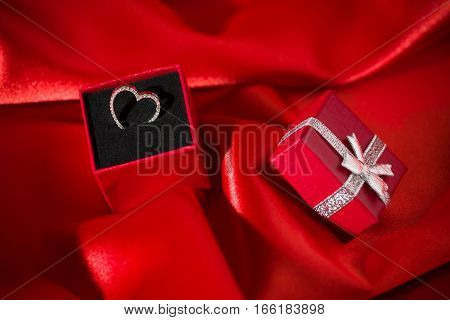 Heart pendant in a red gift box over a red satin background