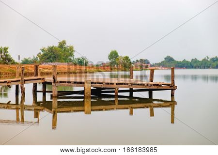 Landscape with wooden pier on the Troav Kot Lake, Cambodia. Sunset in pastel colors.