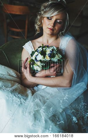 A Tender Bride Wearing Lace Dress Daydreams Holding A Bouquet In Her Arms