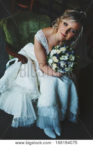 An Attractive Bride Sits In Vintage Green Chair Holding A Bouquet