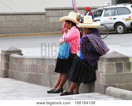 Cajamarca Peru - January 20 2017: Two Peruvian women with sombreros waiting in the Plaza in Cajamarca Peru on January 20 2017