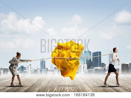 Two businesswomen outdoors playing tag of war game