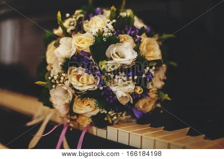 A Wonderful Bride's Bouquet Of White Roses And Violets Lies On The Piano