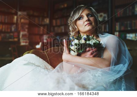 Bride Holds Her Bouquet Sitting  Thoughtful In An Old Big Chair In The Library
