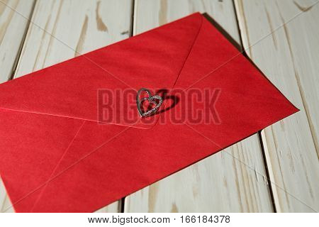 Silver heart pendant on a red envelope over a wooden background