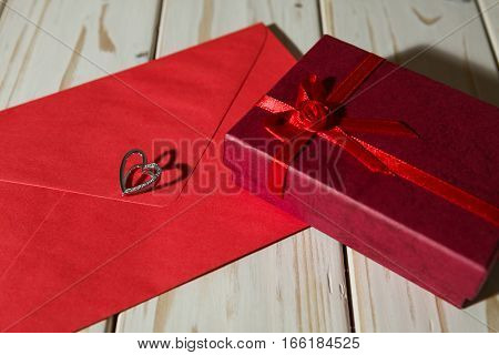 Silver heart pendant on a red envelope and gift box over a wooden background