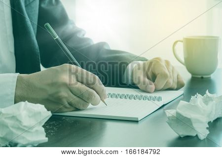 Man Writing In Notebook With Pencil And Paper Ball.