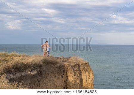 son shows his hand on a hill by the sea