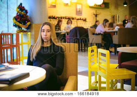Woman In A Cafe. Young Girl Sitting At A Table In A Black Dress