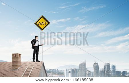Man in suit and helmet holding yellow signboard. Mixed media