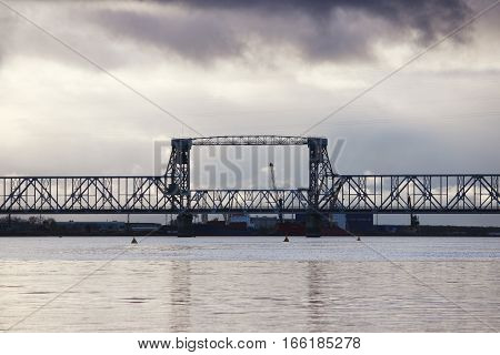 white cumulus clouds pass bridge over the Northern Dvina River