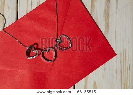 Closeup of silver heart pendants on a red envelope over a wooden background