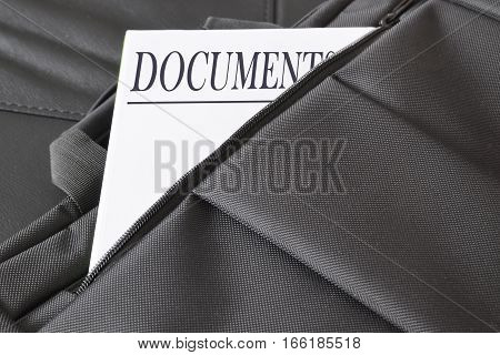 Open briefcase with some documents in it. A paper with the title DOCUMENTS written on it. Empty copy space for Editor's text.