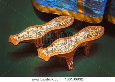 Ancient shoes wood heels against the blue dresses
