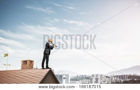 Young businessman in suit and helmet on roof edge. Mixed media
