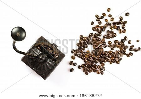 Close up of roasted coffee beans isolated on white background and an old coffee grinder