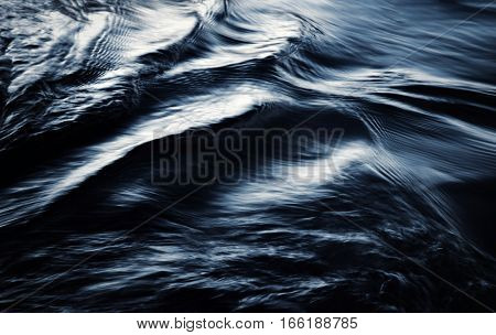 abstract background dark blurred ripples on the lake early evening