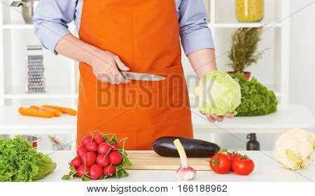 Mid section of a man preparing to chop cabbage in the kitchen at home.