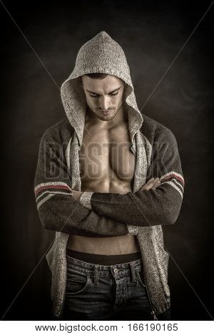 Confident, attractive young man with open vest on muscular torso, ripped abs and pecs. On dark background