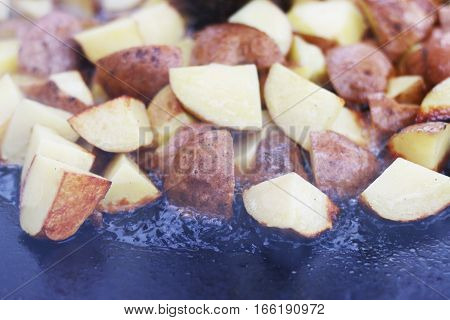Frying raw potato in sunflower oil on large pan. Cooking potatoes