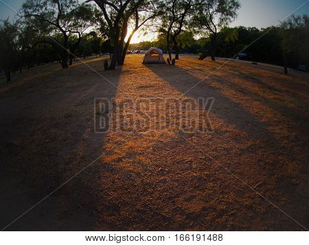 A tent at a campsite in the setting sun at Enchanted Rock State Park in Texas taken with a fisheye lens