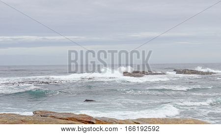 Rock landscape in South of the Cape Peninsula in South Africa, surf on the Atlantic coast near the Cape of Good Hope, rocks on land and underwater