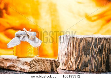 Honey in little glass jar on rustic wood stand next to other one