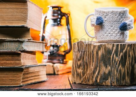 Teacup wearing wool sweater on wood stand. Book stack next to it on the table. Lamp on the background. Concept of cozy home reading