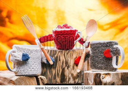 Pair of big mugs and one small cup wearing sweaters on wooden stands. The kid cup holding  spoon and fork