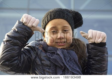 Cute little girl with cap and scarf play outdoors