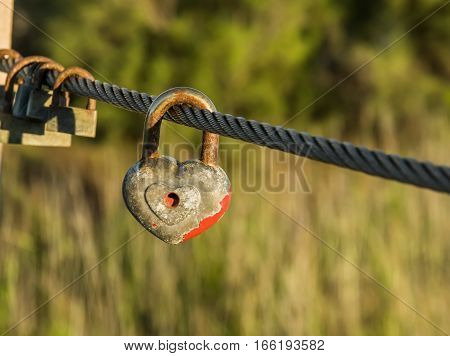 Heart shaped padlock with peeled off red paint in enlarged view and other old rusty padlocks as symbol of eternal love hanging on metal cable. Romance concept. Natural blurred background.