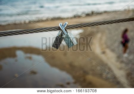 Pair of coupled padlocks as symbol of eternal love hanging on bridge metal cable in front of beach. Romance concept. Blurred background with silhouette of young girl.