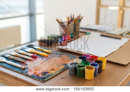 Angle view picture of an old palette with oil paints and gouache set. Clean painter workplace ready for drawing
