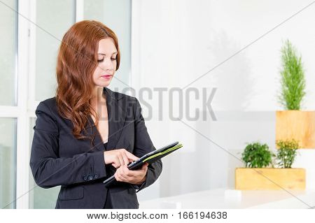 Young businesswoman in modern bright office holding the tablet with a list of tasks. Business concept of office work