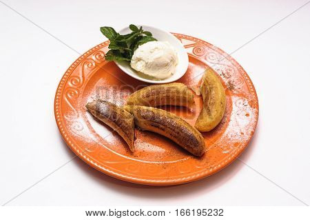 Baked bananas with ice cream on a plate with mint on a white background
