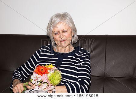 Beautiful senior woman sitting and holding flowers.