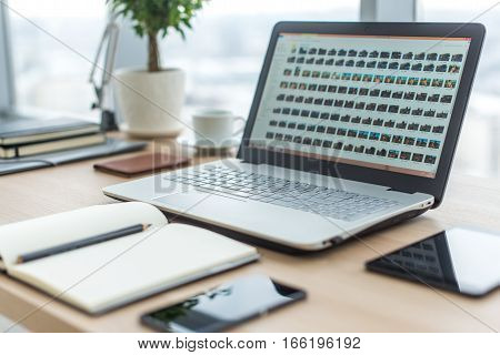 Sideview of office desktop with blank laptop and various tools