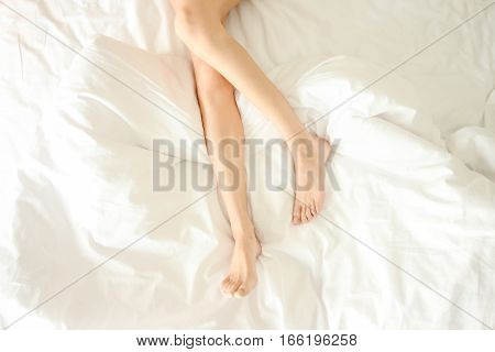 Beautiful female legs not covered top view void. Woman sticks her legs in white bed. Naked legs with white pedicure on end of bed. Some free space