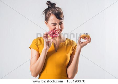 Young funny brunette model with donuts posing studio shot on white background, not isolated.