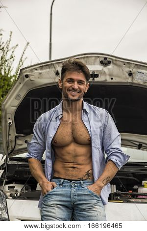 Macho handsome smiling man with his shirt unbuttoned to show his muscular body leaning nonchalantly against the grill of his car with the bonnet open