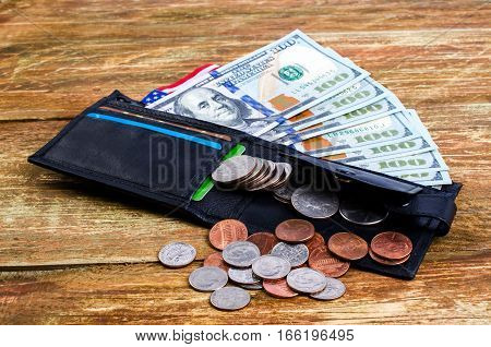 Different coins in wallet american flag and banknotes hundred dollars. On a wooden surface.