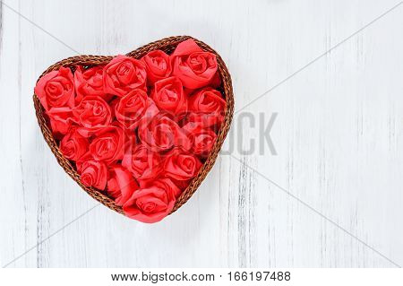 Heart of red paper roses for Valentines day on a white wooden background with space for text