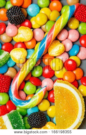 Mixed colorful fruit bonbon close up on gray wooden background