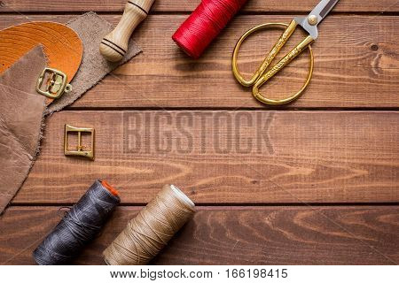 leather craft instruments on wooden background top view.