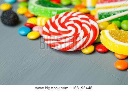 Mixed colorful fruit bonbon on gray wooden background