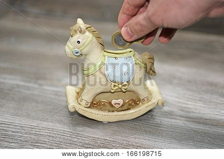 Moneybox in the form of a horse. Located on wooden background.