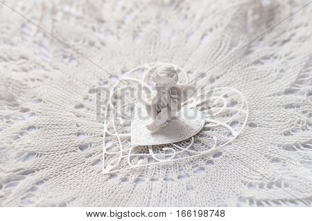 Still life in gentle tones with a small figure of  angel sitting on paper heart on a lace napkin, soft focus